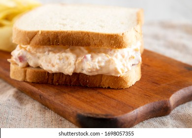 Homemade Tasty Pimento Cheese Sandwich with chips on a rustic wooden board, side view. Close-up.