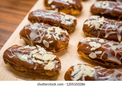 Homemade Tasty Vanilla Eclairs glazed with Milk Chocolate and decorated with Almonds Nuts