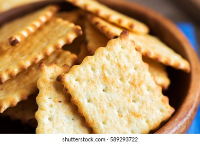 Homemade thin crispy cheesy crackers with sesame seeds in rustic wooden bowl - fresh organic homemade baking cheese crackers snack