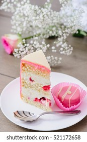 Homemade three layered cake with raspberry inside and pink candy on a white plate
