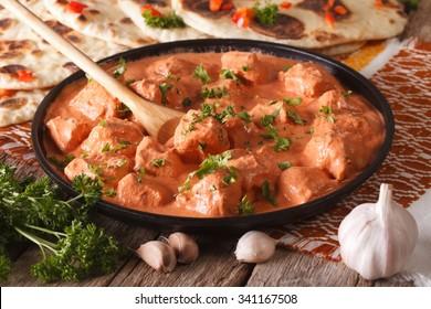 Homemade tikka masala chicken close-up in a black bowl. horizontal