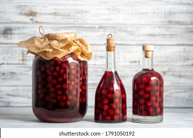 Homemade tincture of red cherry. Berry alcoholic drinks concept. Homemade red wine made from ripe cherries in glass bottles and jars on white wooden background, Ukraine