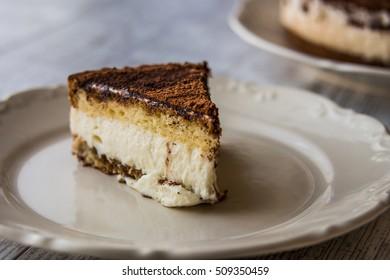 Homemade Tiramisu Cake on a white wooden surface.