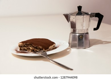 Homemade tiramisu, in a white ceramic plate, isolated on white background. Traditional Italian dessert, with cocoa, coffee, mascarpone and biscuits. Fork in steel and Italian mocha pot.
