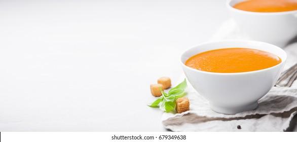 Homemade tomato cream soup in bowls  (or gazpacho) over concrete background