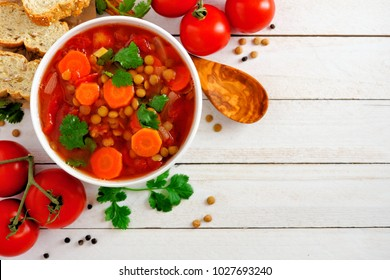 Homemade tomato, lentil soup, above view corner border with copy space on a white wood background
