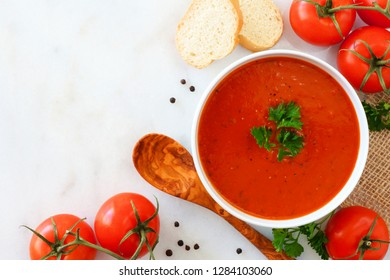 Homemade tomato soup. Above view, corner border with copy space on a bright granite background.