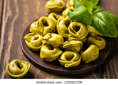 Homemade Tortellini with spinach, cheese and ricotta on wooden board. Gluten free italian food concept.