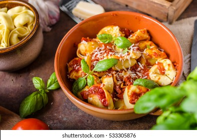 Homemade tortellini with tomato sauce, herbs and garlic in, topped with parmesan cheese