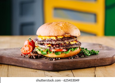 Homemade traditional burger with beef,  tomato, cheese and lettuce on textured background. Fast food concept. Copy space