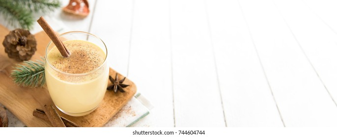 Homemade traditional Christmas eggnog drink in a glass with ground nutmeg, cinnamon and decorating items on white wood table, preparing for celebrating festive holiday season - banner with copy space