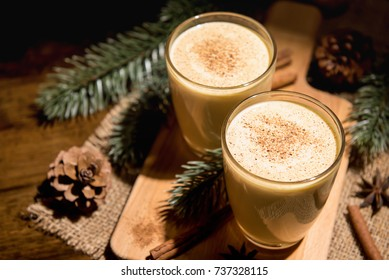 Homemade traditional Christmas eggnog drinks with ground nutmeg, cinnamon and decorating items on wood table, preparing for celebrating festive holiday season