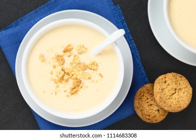 Homemade traditional Danish cold buttermilk koldskal dessert soup with pieces of crisp kammerjunker cookie on top (Selective Focus, Focus on the top of the dessert)