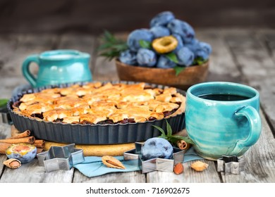 Homemade traditional plum pie with cinamon and almonds with coffee on old wooden background