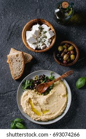 Homemade traditional spread hummus with chopping olives and herbs on blue plate, served with bread, olives, feta cheese, olive oil, spoon on black texture background. Mediterranean snack. Flat lay