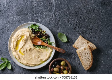 Homemade traditional spread hummus with chopping olives and herbs on blue plate, served with bread, olives variety, olive oil and wood spoon on black texture background. Mediterranean snack. Flat lay.