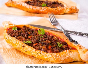 Homemade traditional Turkish meal pide stuffed with meat and sauce