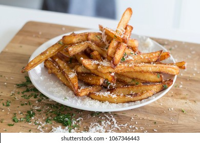 homemade truffle french fries with parsley parmesan truffle oil on wooden cutting board