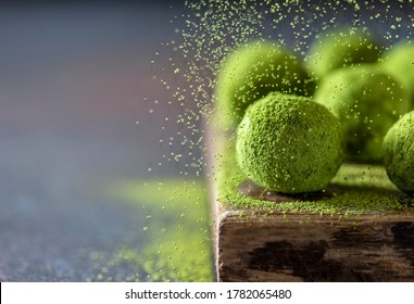 Homemade truffle sweets with matcha green tea on a dark background. Raw energy balls. Selective focus, copy space