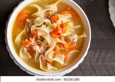 Homemade Turkey Noodle Soup top view on dark wood