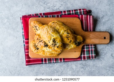 Homemade Turkish Pastry Pogaca with Cumin Seeds / Black Sesame and Cheese on Wooden Board.