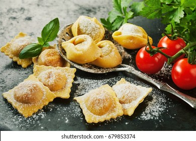 Homemade uncooked freshly prepared Italian ravioli pasta with fresh basil and tomatoes in a rustic kitchen in a close up view
