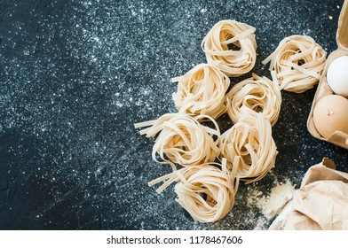 Homemade uncooked tagliatelle pasta on a black background