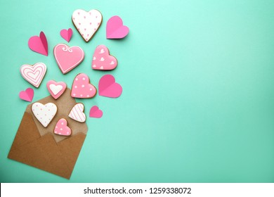 Homemade valentine cookies with envelope on mint background