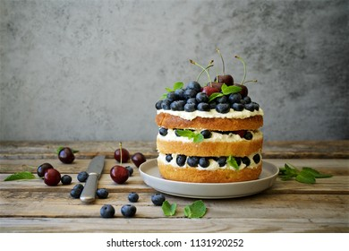 Homemade vanilla cake with berries and fruits. Wooden planks food background