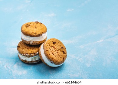 Homemade vanilla ice cream sandwiches with chocolate drops cookies on blue background. Copy space