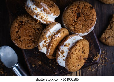 Homemade vanilla ice cream sandwiches with chocolate drops cookies on dark background. Copy space