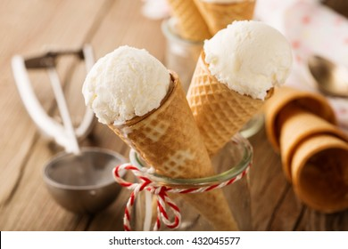 Homemade vanilla ice cream in waffle cones on rustic wooden background, selective focus. Summer time