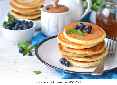 Homemade vanilla pancakes with syrup and blueberries for breakfast. Good morning!