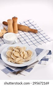 Homemade varenyky Ukrainian traditional dish. Perogy, stuffed dumplings served on white plate. Ukrainian cuisine. Background with food and decorations.