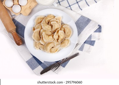 Homemade varenyky Ukrainian traditional dish. Top view. Perogy, stuffed dumplings served on white plate. Ukrainian cuisine. Background with food and decorations.