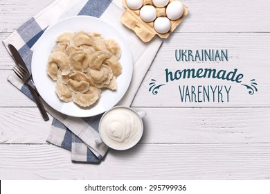 Homemade varenyky Ukrainian traditional dish. Top view. Perogy, stuffed dumplings served on white plate. Ukrainian cuisine. Background with food, typography and decorations.