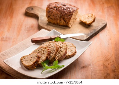 homemade veal meatloaf with cutting board