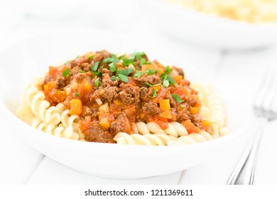 Homemade vegan bolognese sauce made with soy meat, fresh tomatoes, onion and garlic served on fusilli pasta and sprinkled with parsley (Selective Focus, Focus in the middle of the image)