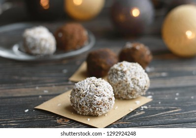 Homemade vegan cocoa sweets dessert. Dates, coconut raw balls candy on brown wooden table background. Healthy food. Recipe for brown homemade chocolates.