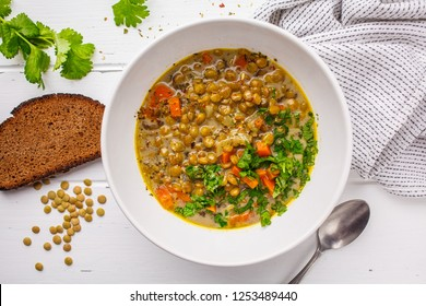 Homemade vegan lentil soup with vegetables and cilantro, white wooden background, top view. Indian vegetarian cuisine.