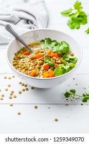 Homemade vegan lentil soup with vegetables and cilantro, white wooden background. Indian vegetarian cuisine.