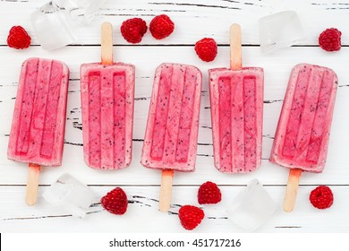 Homemade vegan raspberry coconut milk popsicles - ice pops - paletas with chia seeds on rustic white wooden background