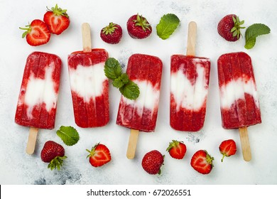 Homemade vegan strawberry coconut milk popsicles - ice pops - paletas on rustic white background