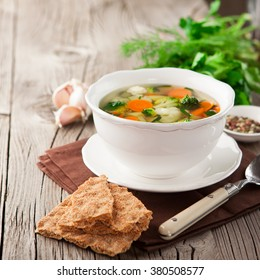 Homemade vegetable soup with broccoli, green peas, carrots and celery in a white bowl on a wooden background in rustic style, selective focus