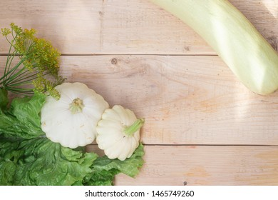 Homemade vegetables. Squash Squash white and lettuce on a wooden background. Green harvest on wooden background. Courgettes on a wooden background. Healthy food. Organic Products