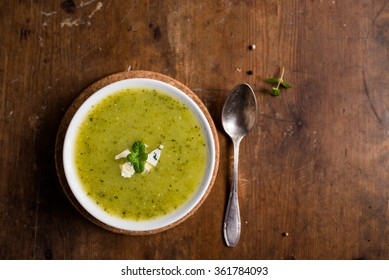 Homemade vegetarian zucchini soup with blue cheese in a white bowl on an old, wooden, brown table