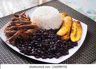 Homemade Venezuelan food. Traditional Venezuelan dish. Pabellon Criollo. White Rice, Black beans,Fried plantains, and Shredded beef