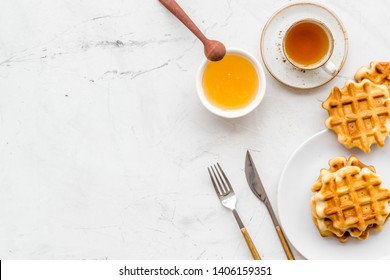 Homemade Viennese waffles with honey and tea, flatware on marble background top view make-up
