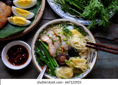 Homemade Vietnam food, egg noodle soup with wontons, colorful food ingredient for this eating as egg, pork, broth, shallot, bean sprout, agaric, vegetable