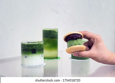 Homemade of wafer sandwich with scoop of Japanese matcha ice cream served with red bean and glasses of matcha latte and matcha with lemon soda on the table. Traditional dessert with selective focus.